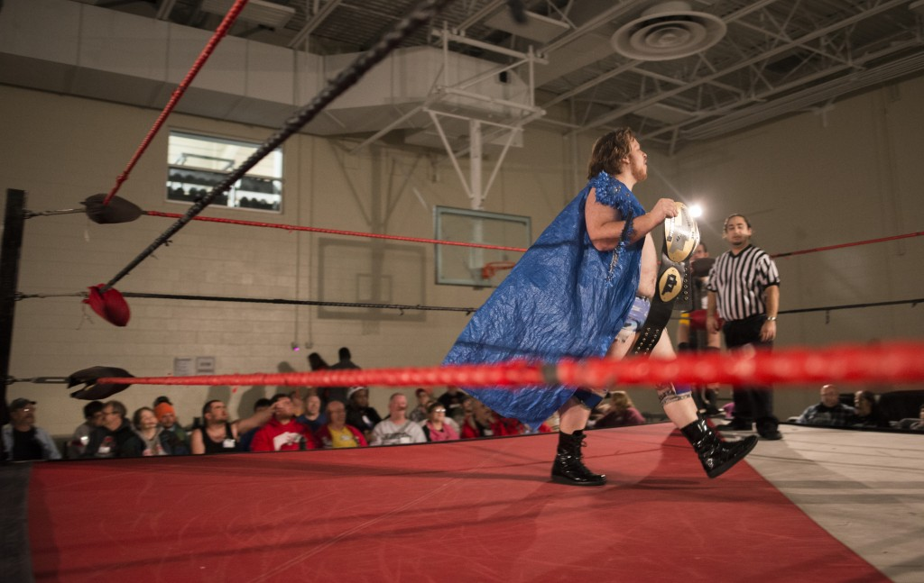 """Ben Blagg, """"Duke Beefhammer,"""" struts across the ring with his wrestling belt and tarp cape during the opening match of the XWE Pro Wrestling event as referee, Tim Porras, and the audience watch on at Hocking College on Friday, October 21, 2016 in Nelsonville, Ohio. Blagg is 26-years-old and has been wrestling for the past three years. (Kelsey Brunner/WOUB)"""
