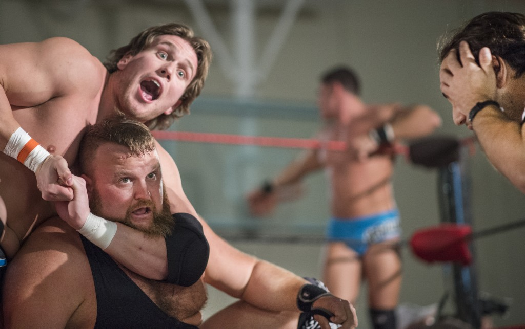 Darin Lyles, left, makes a face toward the cheering crowd while holding Jock Samson in a choke hold while Clay Kiene addresses the audience outside the ring and referee Tim Porras holds his face in mock dismay in the Hocking College Student Center during the XWE Pro Wrestling event on Friday, October 21, 2016 in Nelsonville, Ohio. (Kelsey Brunner/WOUB)