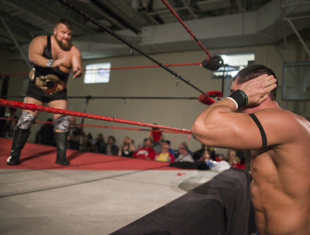 """Jock Samson, left, heckles Clay Kiene about his """"steroid use"""" for the entertainment of the audience before a team wrestling match at Hocking College during the XWE Pro Wrestling match on Friday, October 21, 2016 in Nelsonville, Ohio. This group of wrestlers have a wide range of times as performers, Samson has been wrestling for 12 years and Kiene for a year and a half. (Kelsey Brunner/WOUB)"""