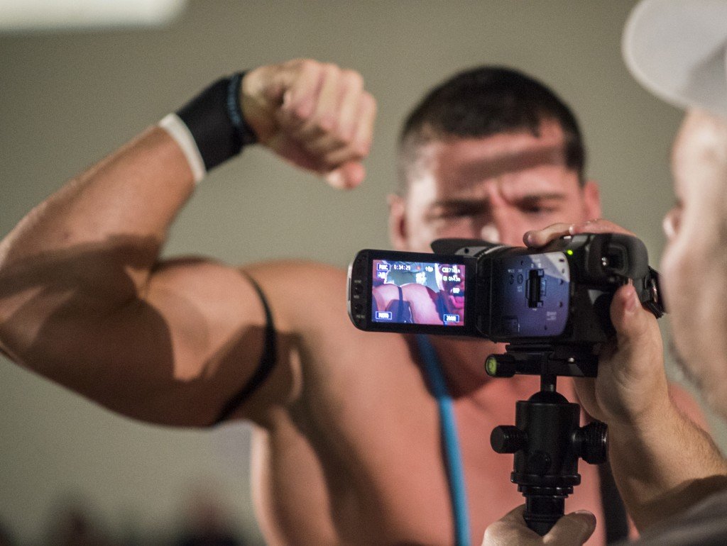 """Clay Kiene, 22, flexes his muscles into the video camera before entering the ring of his team match during the XWE Pro Wrestling event at Hocking College on Friday, October 21, 2016 in Nelsonville, Ohio. Kiene has been wrestling for a short year and a half and wrestles under the name """"Clay Jackson."""" (Kelsey Brunner/WOUB)"""