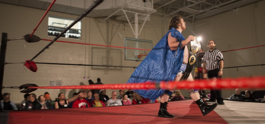"Ben Blagg, ""Duke Beefhammer,"" struts across the ring with his wrestling belt and tarp cape during the opening match of the XWE Pro Wrestling event as referee, Tim Porras, and the audience watch on at Hocking College on Friday, October 21, 2016 in Nelsonville, Ohio. Blagg is 26-years-old and has been wrestling for the past three years. (Kelsey Brunner/WOUB)"