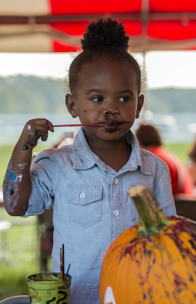 Lyric Powell, 2, paints her lips with black paint after finishing painting her pumpkin in the Make and Take tent during the 46th annual Bob Evans Farm Festival on Saturday, Oct., 15, 2016 in Rio Grande, Ohio. (Kelsey Brunner/WOUB)