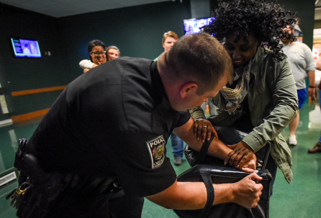 Imani Sellers, 21, kneeing proactive padding held by Ohio University Police officer, Brandon King, during the Queer Self Defense night, sponsored by the Student Senate and LGBT Center, in the Bobcat Lounge in Baker Center at Ohio University on October, 27 2016.  (Carolyn Rogers/WOUB)
