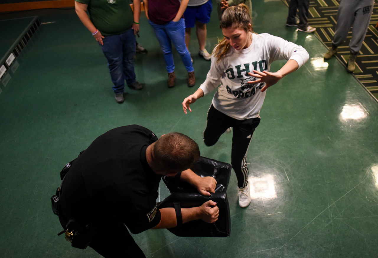 Kate Stanley, 21, kicking proactive padding held by Ohio University Police officer, Brandon King, during the Queer Self Defense night, sponsored by the Student Senate and LGBT Center, in the Bobcat Lounge in Baker Center at Ohio University on October, 27 2016.  Officer King has worked at Ohio University for 15 years and has taught self defense classes over the pass 14 years. (Carolyn Rogers/WOUB)