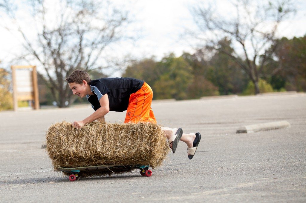A boy rides a hay bale on top of skateboard at the Athens Harvest Festival on October 16, 2016. (Erin Clark/WOUB)