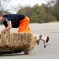 A boy rides a hay bale on top of skateboard at the Athens Harvest Festival on October 16, 2016.