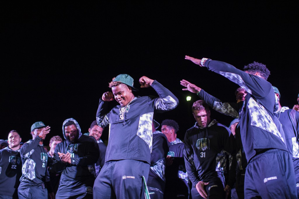 A member of the football team flexes as his teammates cheer him on at the Yell Like Hell event at Ohio University on October 6, 2016. (Michael Swensen/WOUB)