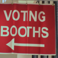 A red sign with white lettering that reads voting booths