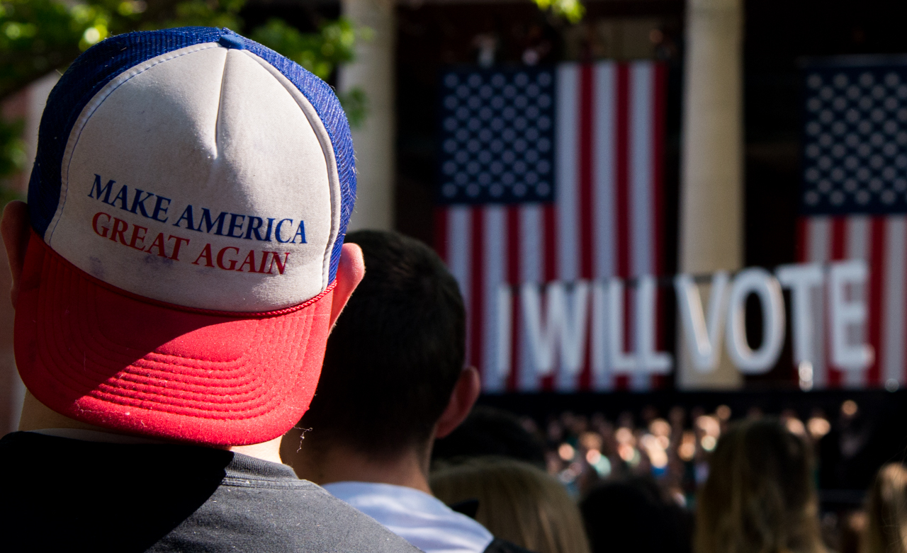An Ohio University student, wearing a make america great again hat, which is the campaign slogan for the republican nominee, Donald Trump, listening to Bill Clinton speak on college green at Ohio University in Athens, Ohio, on October 4, 2016. (Carolyn Rogers/ WOUB)