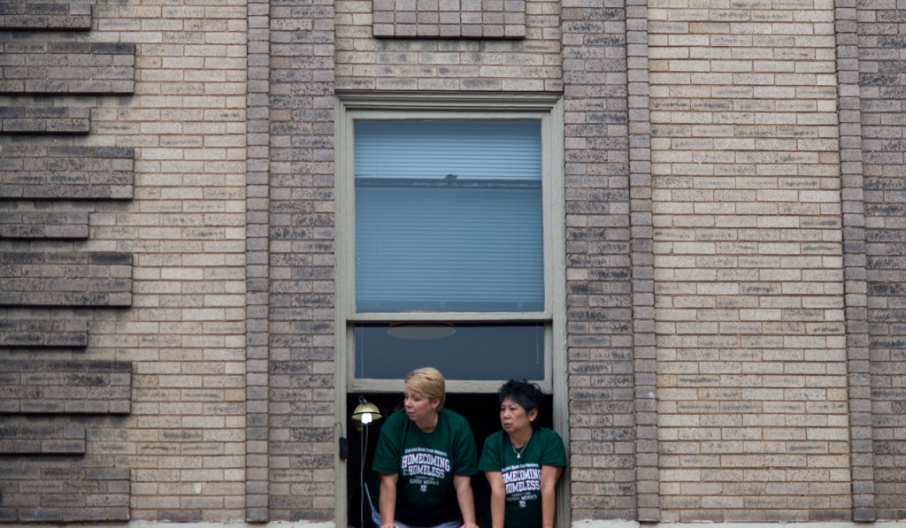 Two women watching the Ohio University parade from a window above the College Bookstore on Court Street in Athens, Ohio, on October 8, 2016. (Carolyn Rogers/WOUB)