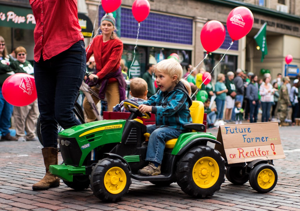 A young boy drives his toy tractor behind the Athens Real estate company float in the Ohio University Homecoming parade in Athens, Ohio, on October 8, 2016. (Carolyn Rogers/WOUB)