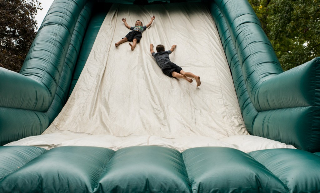 Two kids slide down one of the inflatable blow-ups during a tailgate party before the Homecoming game in Athens, Ohio, on October 8, 2016. (Carolyn Rogers/WOUB)