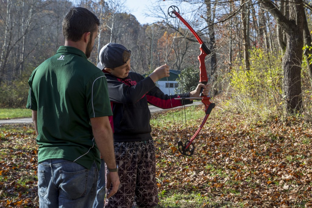 Chad Gatt, from the Raccoon Creek Partnership, teaches Zach Mullins, attendee to the event, how to hold the bow at the Raccoon Creek Partnership Archery Day Camp on Saturday, November 5, 2016, at Waterloo Aquatic Education Center, New Marshfield, Ohio. (Jorge Castillo Castro/WOUB)
