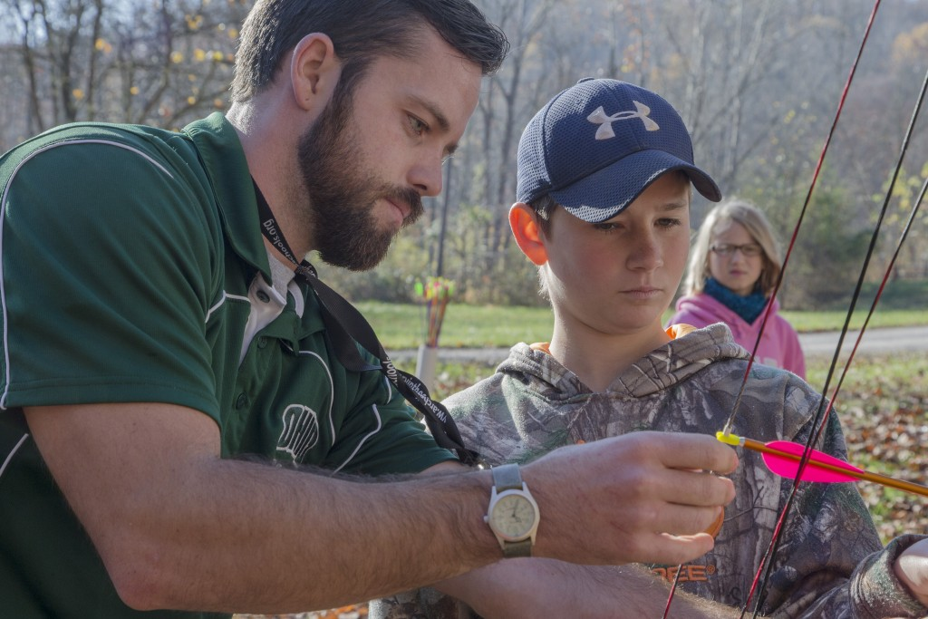 Chad Gatt, from the Raccoon Creek Partnership, and Brice Hale, attendee to the event, review the use of the bow at the Raccoon Creek Partnership Archery Day Camp on Saturday, November 5, 2016, at Waterloo Aquatic Education Center, New Marshfield, Ohio. (Jorge Castillo Castro/WOUB)
