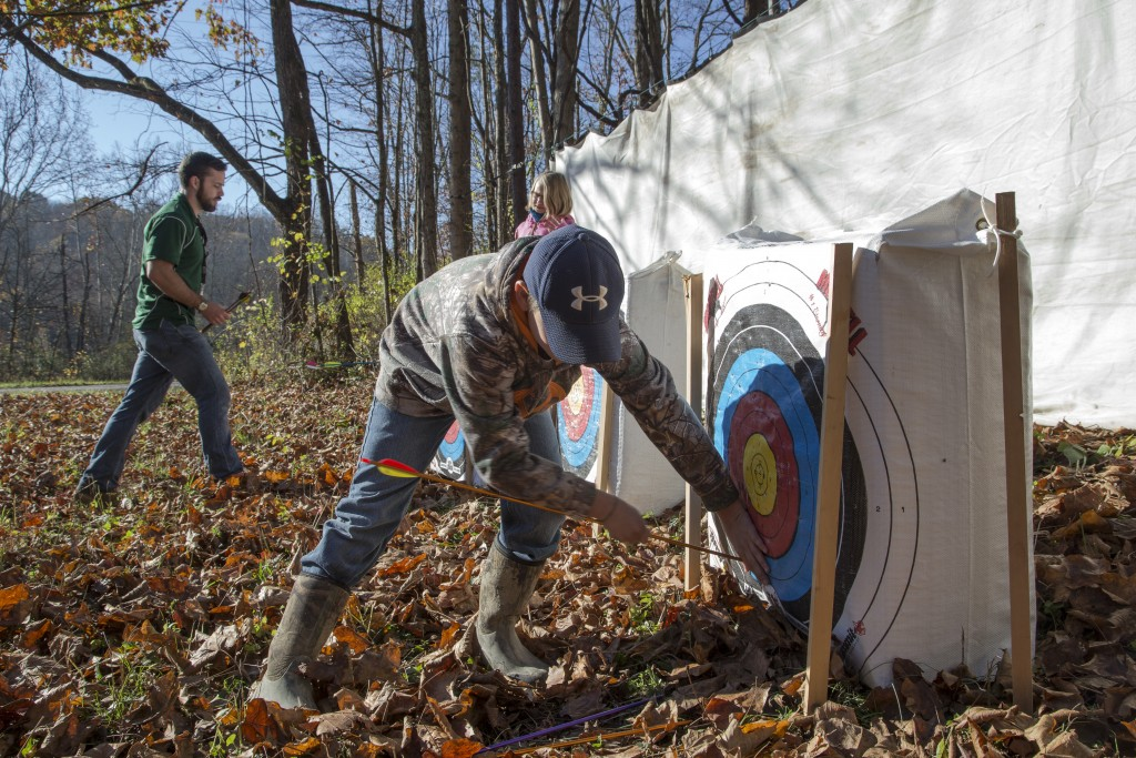 Brice Hale, 13 and attendee to the event, remove the arrows from the targets at the Raccoon Creek Partnership Archery Day Camp on Saturday, November 5, 2016, at Waterloo Aquatic Education Center, New Marshfield, Ohio. (Jorge Castillo Castro/WOUB)