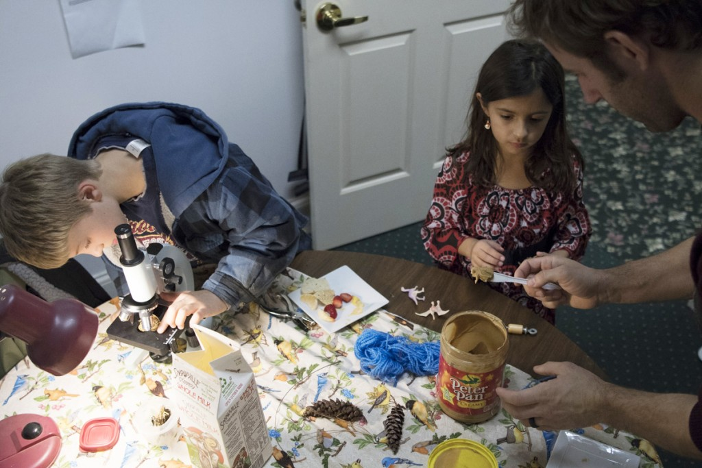 Clara Arauz, middle, makes bird feeders with environmental educator Joe Brehm, right, as Lewis Broeckner adjusts a microscope with a butterfly in it at the Rural Action Holiday Open House on December 13, 2016. (Robert McGraw/WOUB)
