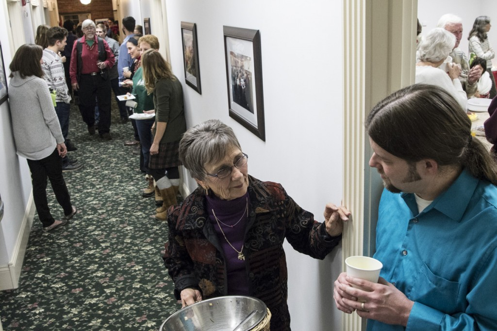 Program Director of OH SUN Luke Sulfridge, right, talks with retiree and Rural Action volunteer Barbara Keyes, left, about the growth of solar energy in Ohio during a packed house at the Rural Action Holiday Open House on December 13, 2016. (Robert McGraw/WOUB)