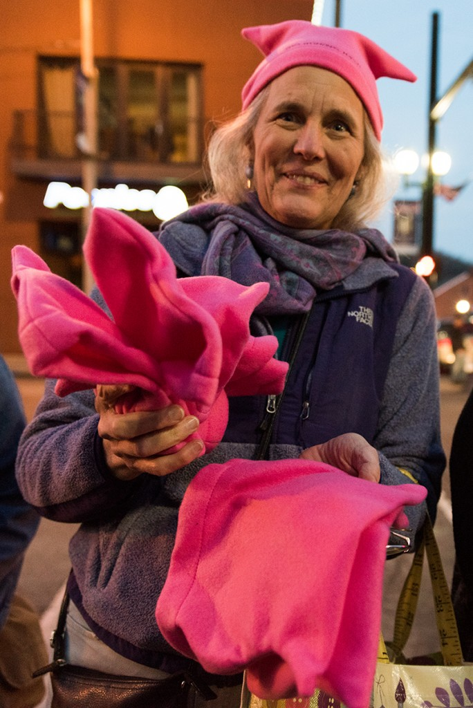 Wenda Sheard, local community member and board member of the UCM, is selling pink hats in exchange for donations at the Athens Women's March gathering outside of the Athens County courthouse on January 20, 2017. (Nickolas Oatley/WOUB)
