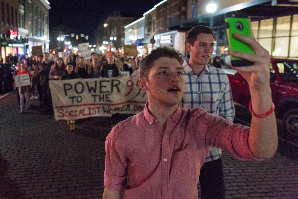 Donald J. Trump supporters Snapchat and take videos of themselves dancing in front of the Athens Women's March in the middle of Court Street on January 20, 2017. (Nickolas Oatley/WOUB)
