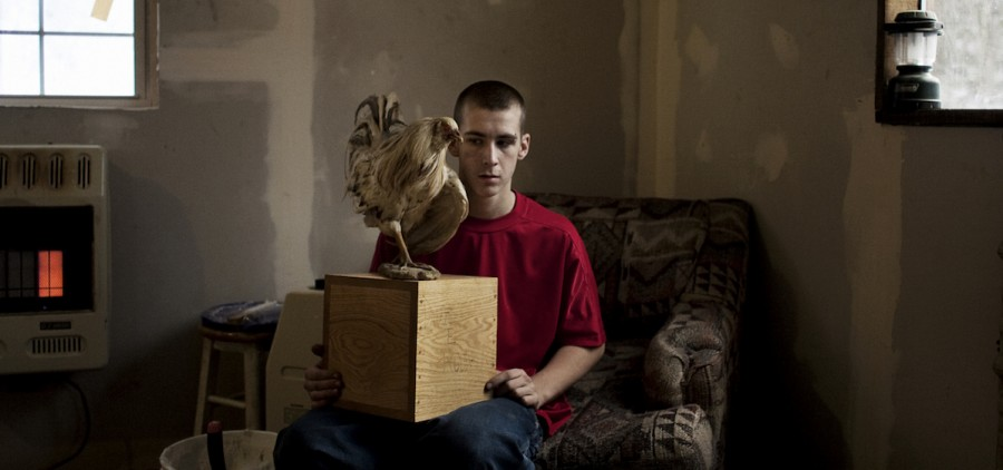 """Tylor Woodrum, 16, holds a box containing his father's ashes on January 30, 2007 in Carbondale, OH. Dave Woodrum was killed in August of 2006 in a high-impact 4-wheeler accident. Dave's family had his body cremated and his favorite cock-fighting rooster mounted on top of the box. This photo is a part of photographer Matt Eich's """"Carry Me Ohio"""" project. (Matt Eich)"""