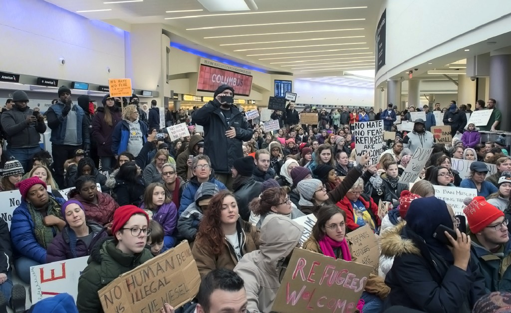 On Sunday, January 29, 2017, 100's gathered at John Glenn Columbus International Airport to peacefully protest President Donald Trump's executive order banning travel to the United States from seven predominantly Muslim countries: Iran, Iraq, Libya, Somalia, Sudan, Syria, and Yemen. Reentry by those carrying visas, or U.S. citizens, that immigrated from those countries, were turned away or detained. This executive order also halts refugee programs for 120 days. These protestors staged a sit-in, and march at the airport, while similar protests occurred at numerous airports across the U.S. (Margo Sabec/WOUB)