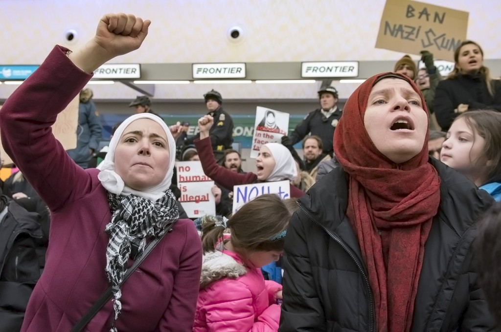 Amina Barhumi (left) and Sumaya Hamadmad (right) gathered with 100's of others on Sunday, January 29, 2017, at John Glenn Columbus International Airport to peacefully protest President Donald Trump's executive order banning travel to the United States from seven predominantly Muslim countries: Iran, Iraq, Libya, Somalia, Sudan, Syria, and Yemen. Reentry by those carrying visas, or U.S. citizens, that immigrated from those countries, were turned away or detained. The executive order also halts refugee programs for 120 days. These protestors staged a sit-in, and march at the airport, while similar protests occurred at numerous airports across the U.S. (Margo Sabec/WOUB)