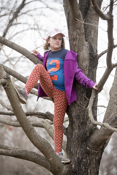 Clemenine Easton, 10-year-old from Columbus, Ohio, views protesters from a nearby tree at the Ross County Women's March on January 21, 2017. (Camille Fine/WOUB)
