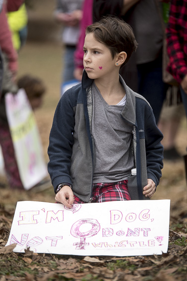 A young protester sits while listening to a speaker at the Ross County Women's March on January 21, 2017. (Camille Fine/WOUB)