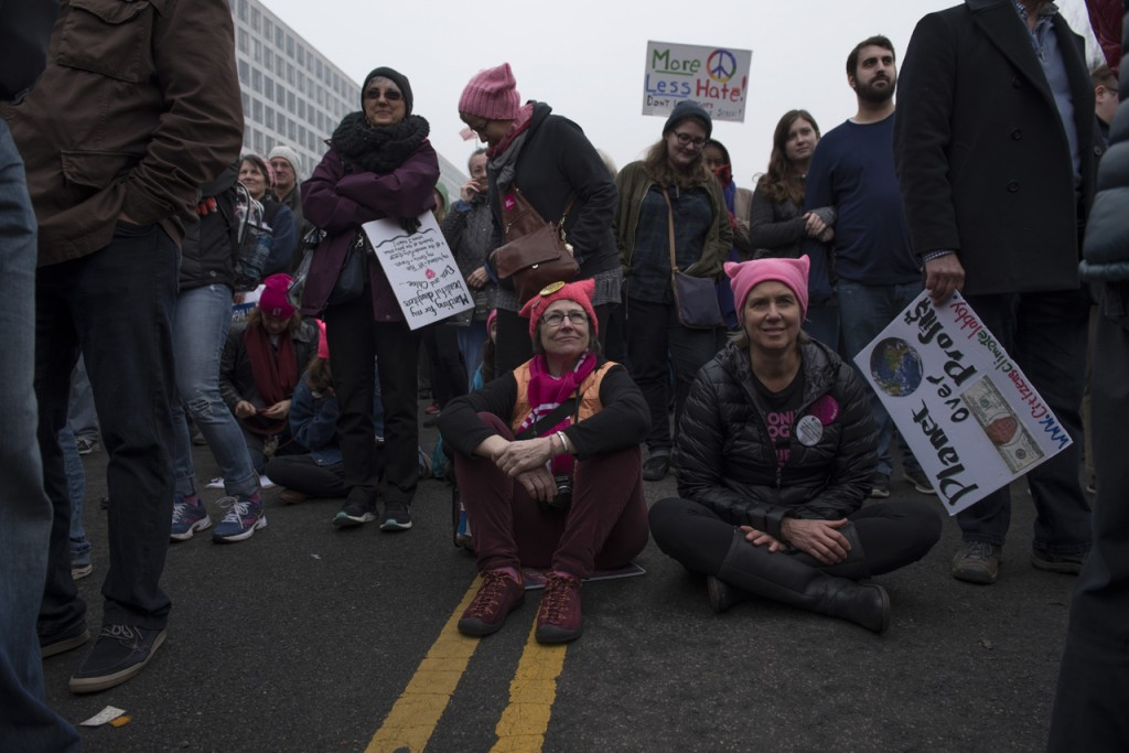 On January 21, 2017, hundreds of thousands participated at the Women's March on Washington, carrying banners, and wearing pink pussy hats. Participants could be seen holding posters, or wearing sashes, stickers, and buttons, that displayed the state they travelled from. Some in less crowded areas rested temporarily on the pavement while listening to the guest speakers; Angela Davis, America Ferrera, Linda Sarsour, Scarlet Johansson, Alicia Keys, Jangle Monae, Gloria Steinem, Ashley Judd, and Madonna to name a few.(Margo Sabec/WOUB)