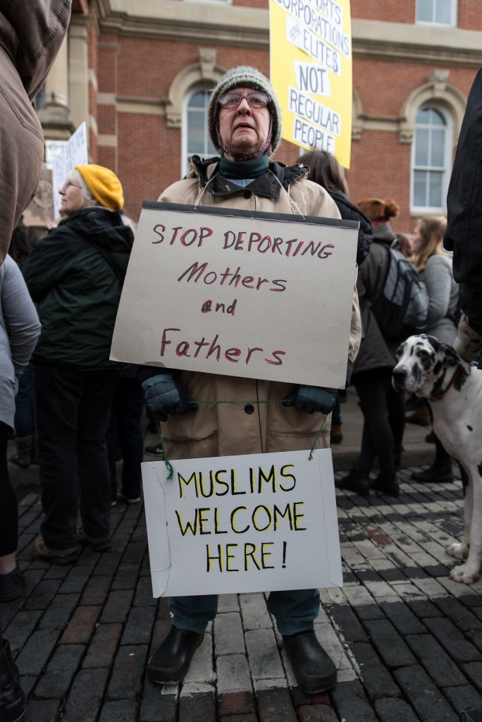 """Jan Griesinger poses for a portrait in the middle of Court Street at the No Ban No Wall Protest. Jan has been a resident of Athens for 35 years and when asked about why she attended the protest she said, """"There is nothing more to say than what's on the sign."""" (Nickolas Oatley/ WOUB)"""