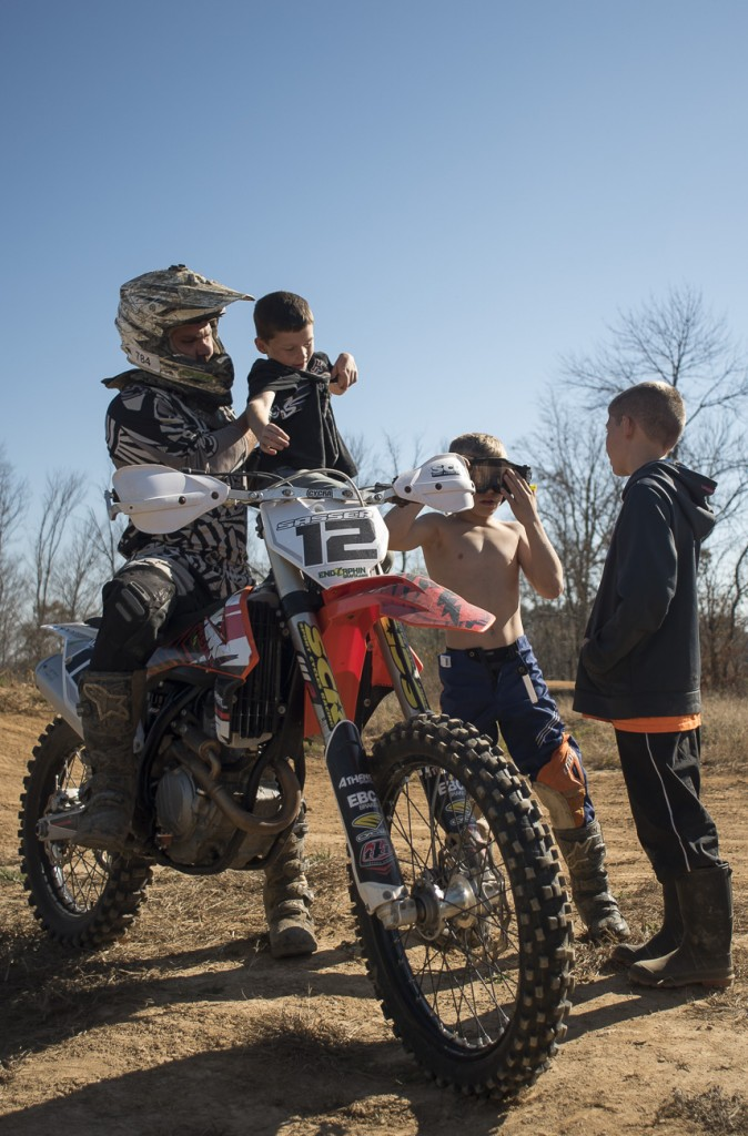 Justin Cunningham picks up his nephew, Ryder Cunningham, while Joseph and Xavier Cunningham compare riding goggles on November 6, 2016.
