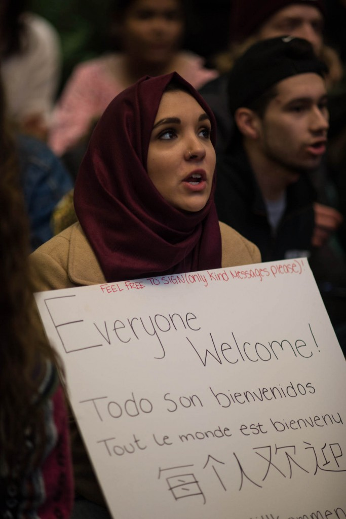 """Alana Adbella, 19, sits on the floor of Baker Center, during the """"No Ban no Wall protest/sit in. Alana  holds a sign with """"Everyone Welcome"""" written in different langauges. The protest was held on February 1, 2017 in Athens, Ohio. (Meagan Hall/WOUB)"""