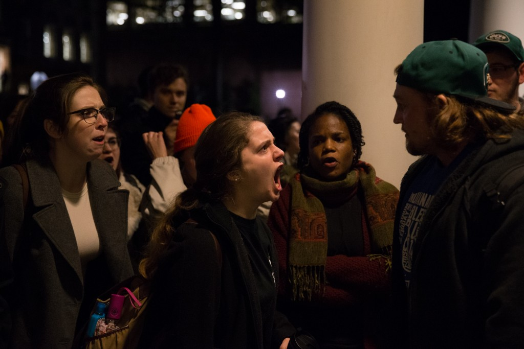 Nancy Mitchell, left, Cecilia Ellis, center, and Monée Stamp, right, argue with Trump supporter, Tommy Russ, far right, during the rally at Baker Center on February 2, 2017. (Michael Johnson/WOUB)