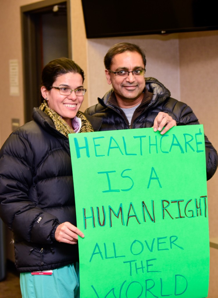 Militza Lozado, DO and Umamahesh Yellamraju, MD display one of many signs made by volunteers for the Healthcare Allies Asylum March in Athens, Ohio on February 3, 2017 (Robert Green/WOUB)