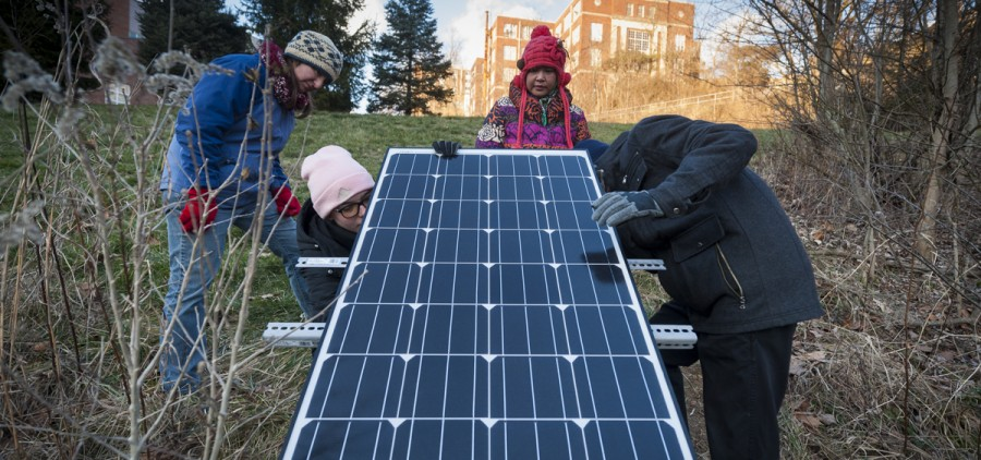Siti Hj Abd Rahman, middle, 34, a graduate student at Ohio University, works on her masters thesis research project with her teammates and colleagues, Nora Sullivan (left), Grace Fuchs (middle-left), and Sebastian Teas (right). They have placed a solar panel that powers a device that collects data on the water quality surrounding Ohio University. (Michael Swensen/WOUB)