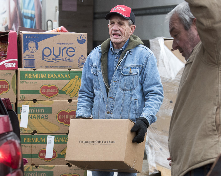 Fred Schorre, a volunteer for the food bank, helps load a car with food in Wellston, Ohio on February 1, 2017. (Camille Fine/WOUB)