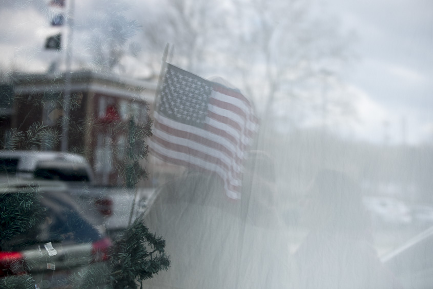 A protester waves a flag in protest of Congressman Bill Johnson in Marietta, Ohio on Febuary 25, 2017. (Camille Fine/WOUB)