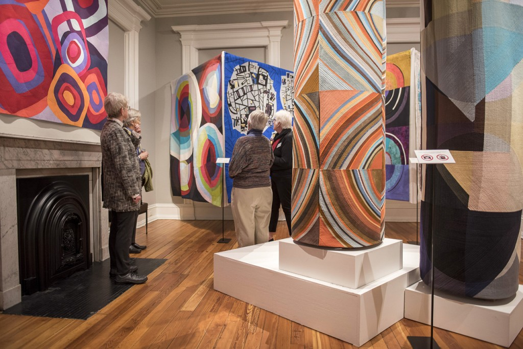 "Visitors to the historic Reese-Peters House, which houses the Decorative Arts Center of Ohio, take a look at the museum's ""Circular Abstractions: Bull's Eye Quilts"" exhibition. (Margo Sabec/WOUB)"
