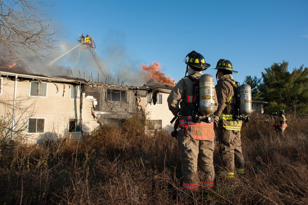 Firefighters wait during a period of low water pressure, allowing the main water nozzles to take priority on February 26th, 2017. (Drake Withers / WOUB)