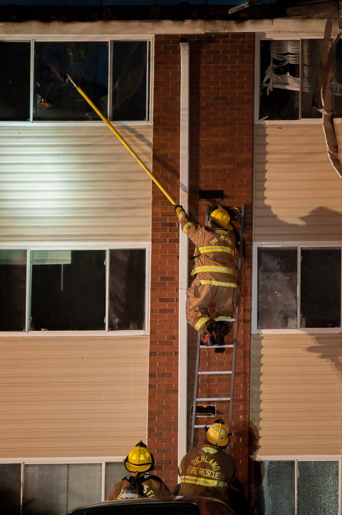 Firefighters break the windows in Carriage Hill building number 12 to spray water directly into the building. (Drake Withers / WOUB)