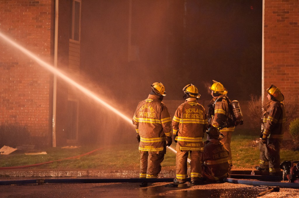 Firefighters spray water into Carriage Hill building number 12 from the parking lot. (Drake Withers / WOUB)