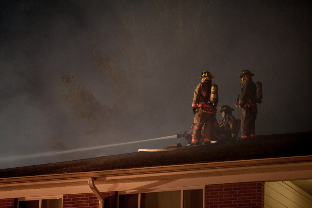 Firefighters spray water into Carriage Hill building number 12 from the roof of an adjacent building. The fire was prevented from spreading to any nearby structure, although building 12 was left in ruins. (Drake Withers / WOUB)