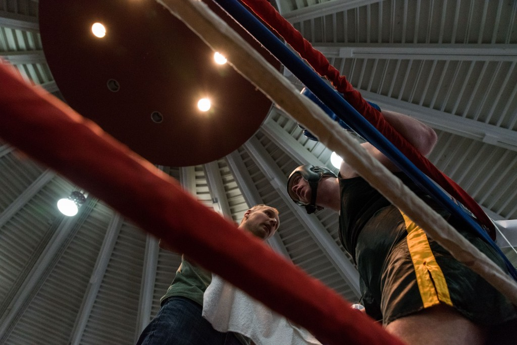 A man stands in the corner with his coach while competing for the Amateur Boxing title. (Nickolas Oatley/WOUB)