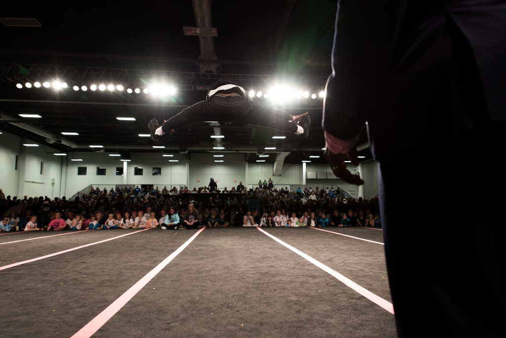 """A man from the crowd goes on stage and competes in the """"Best Toe Touch"""" competition (Nickolas Oatley/WOUB)"""