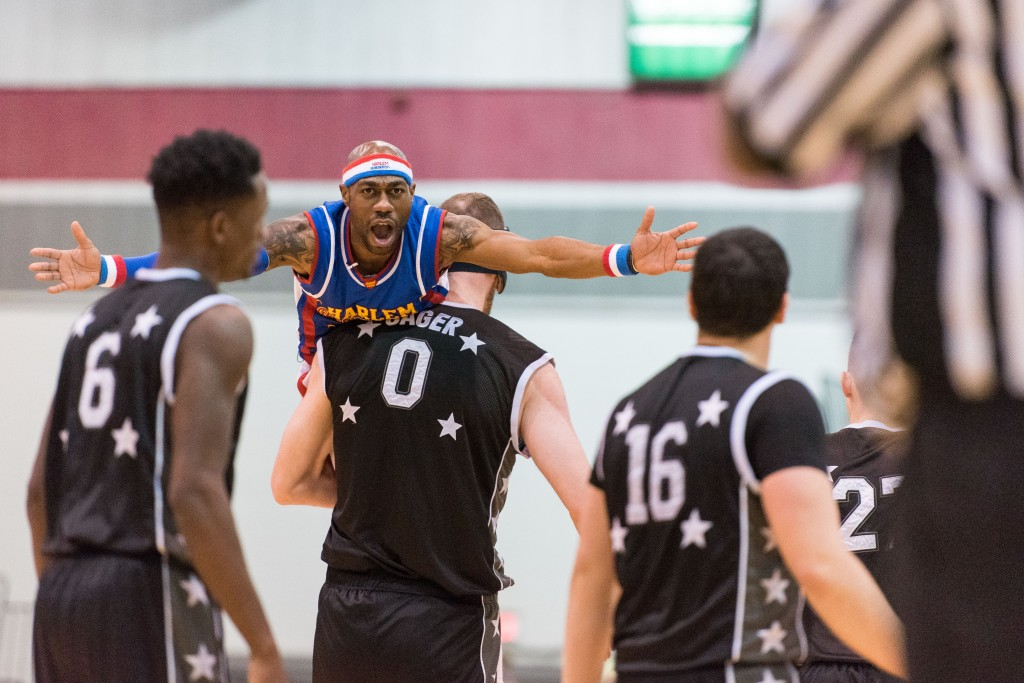 """World All Stars giant """"Cager"""" picks up Harlem Globetrotter """"Firefly"""" as he went up for a layup and carries him down the court. No call was given by the referee on the play.(Nickolas Oatley/WOUB)"""
