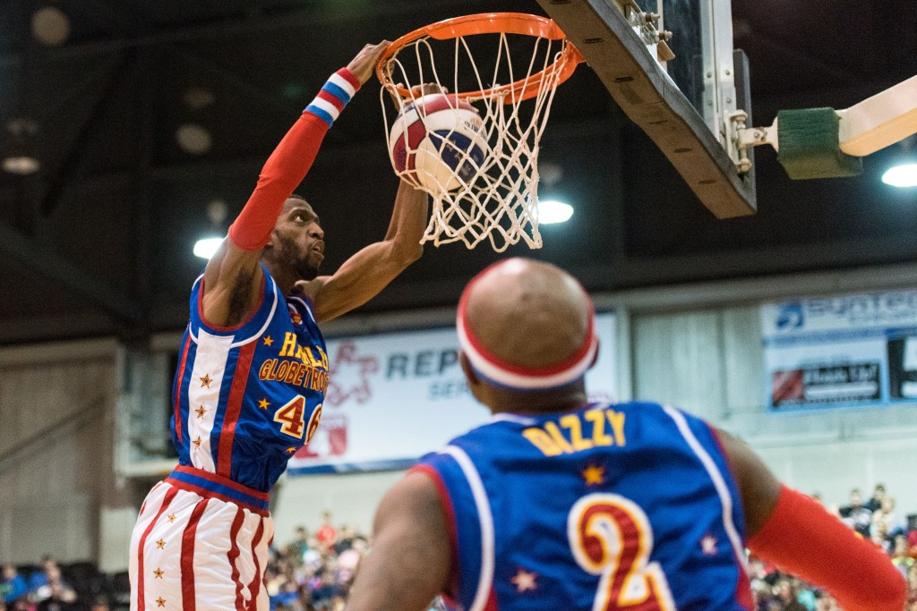 """""""Hot Rod"""" goes up for a slam dunk thrown off of the backboard by teammate """"Dizzy"""" at the Big Sandy Superstore Arena in Huntington, WV on Wednesday, March 1st. (Nickolas Oatley/WOUB)"""