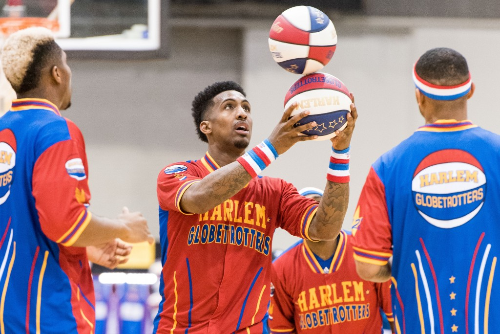 """Harlem Globetrotter """"Bull"""" spins one ball on top of the other at center court. (Nickolas Oatley/WOUB)"""