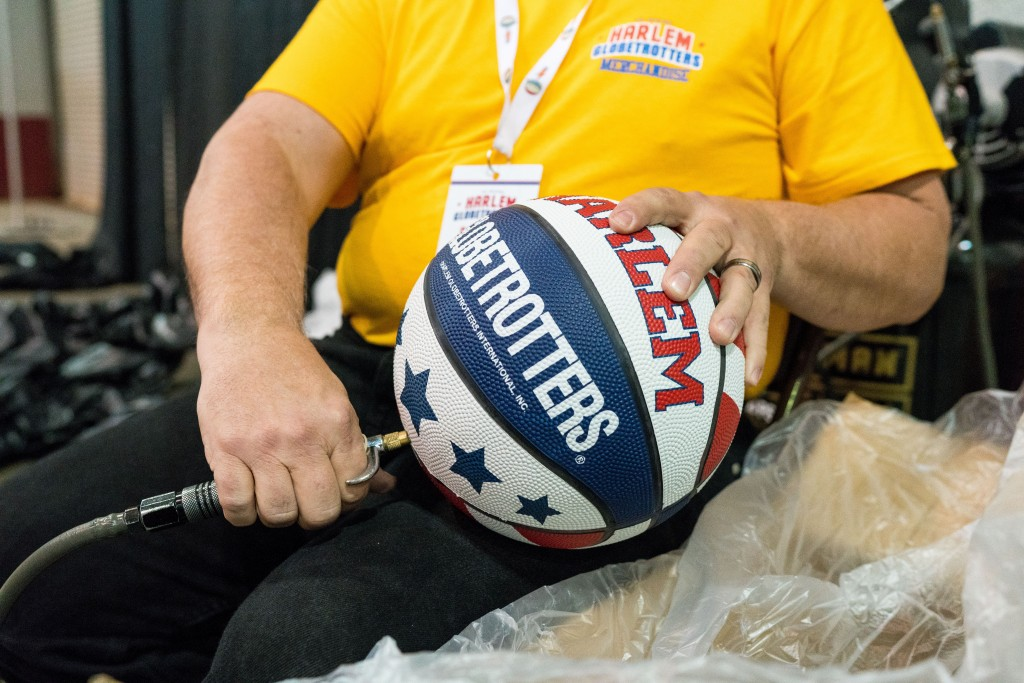 A Harlem Globetrotters Merchandise worker pumps up basketballs for the end of the show when fans have the opportunity to have the balls signed by the Globetrotters. (Nickolas Oatley/WOUB)