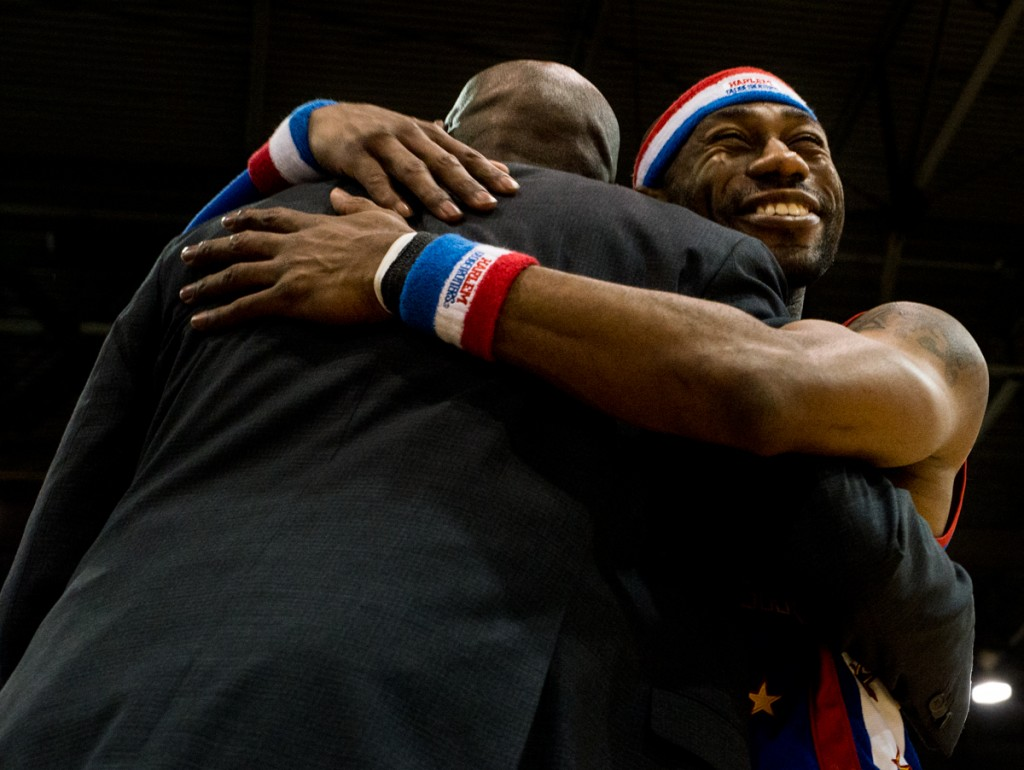Harlem Globetrotter, Firefly, hugging the coach, Barry Hardy, after teasing him about his purse during the game against the World All-Stars at the  Harlem Globetrotters game in the Big Sandy Superstore Arena, in Huntington, West Virginia, on March 1, 2017. (Carolyn Rogers/WOUB)