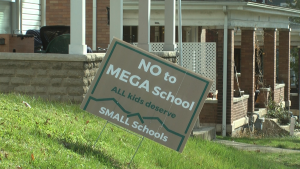"""Signs reading """"No to Mega School"""" are seen in yards around the school district"""